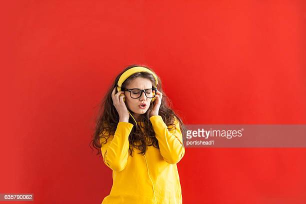 Happy woman with yellow headphones and eyeglasses on red background