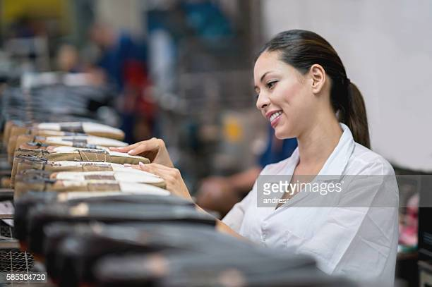 happy woman working at a shoe-making factory - work shoe stock-fotos und bilder