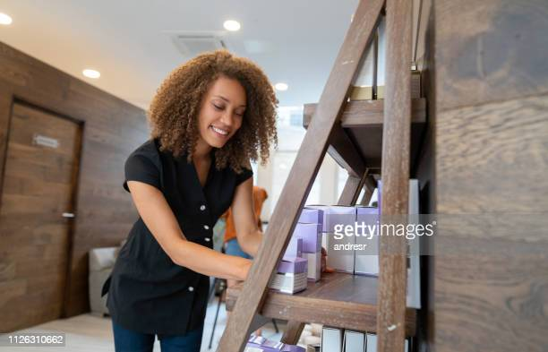 happy woman working at a spa selling beauty products - beauty spa stock pictures, royalty-free photos & images