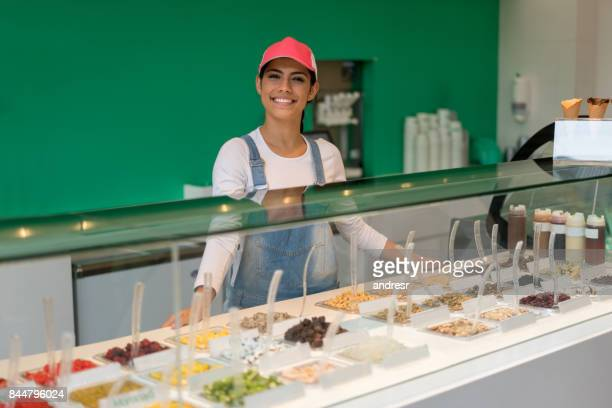 Happy woman working at an ice cream parlor