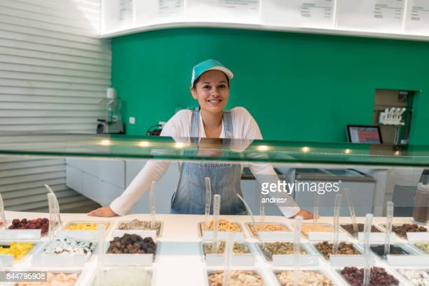 Happy woman working at an ice cream shop