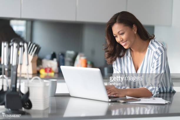 happy woman working online at home using a laptop computer - mid adult women stock pictures, royalty-free photos & images