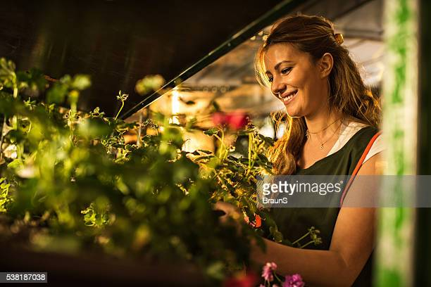 Happy woman working with plants in a garden house.