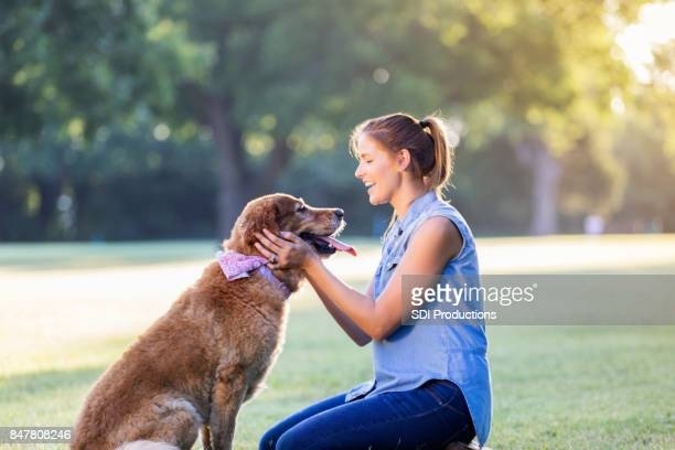 Happy woman works on obedience training with her dog