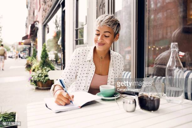 happy woman writing in diary at sidewalk cafe - diary stock pictures, royalty-free photos & images