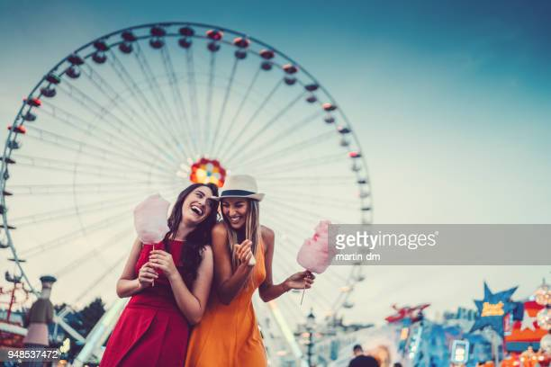 happy women at the amusement park - cotton candy stock pictures, royalty-free photos & images
