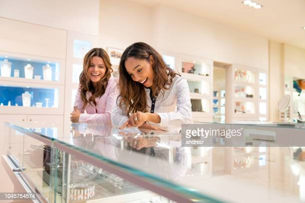 happy women buying jewels at a jewelry store - jewelry store stock pictures, royalty-free photos & images
