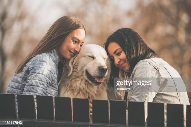 Happy women cuddling their dog in the park