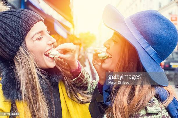 Happy women eating parisian macaroons