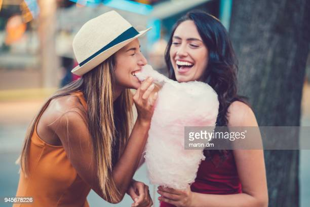 happy women eating pink cotton candy - cotton candy stock pictures, royalty-free photos & images