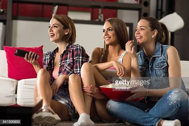 Happy women eating popcorns and watching TV at home.