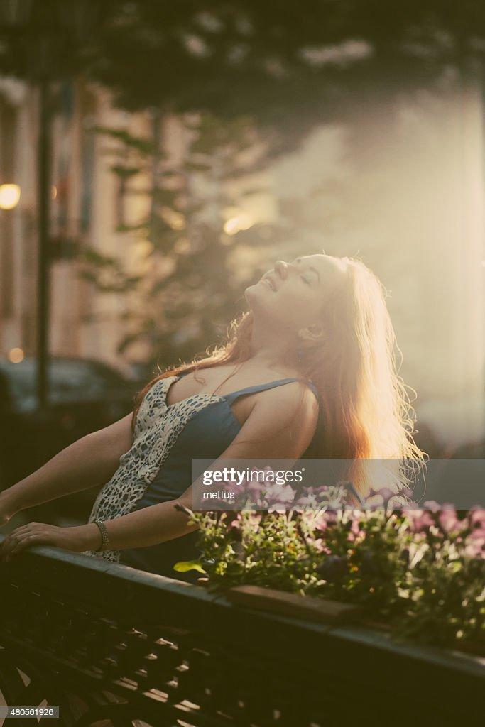 Happy women enjoy summertime in city park backlit shot : Stock Photo