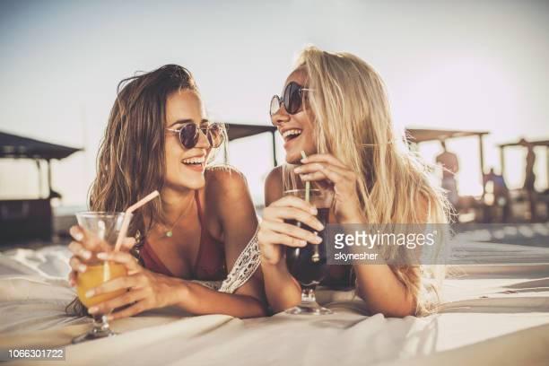 glückliche frauen genießen sie getränke und unterhaltung auf einer liege. - nur frauen stock-fotos und bilder