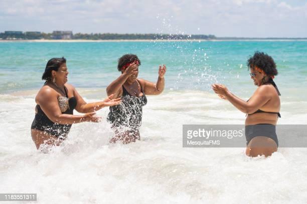 glückliche frauen genießen das meer - dicke frauen am strand stock-fotos und bilder