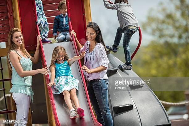 Happy women enjoying with their children on a playground.