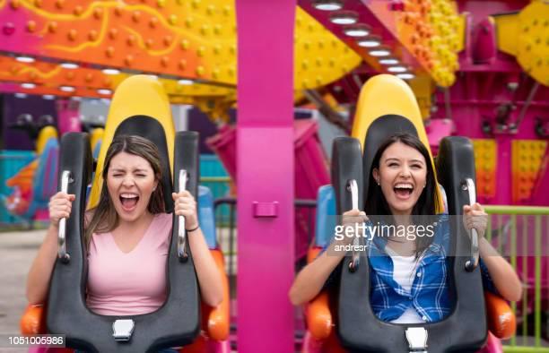 happy women having fun in an amusement park - amusement park ride stock pictures, royalty-free photos & images