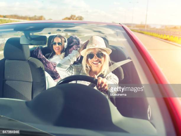 Happy women having fun on a road trip in convertible