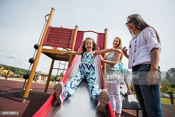 Happy women having fun with kids at the playground.