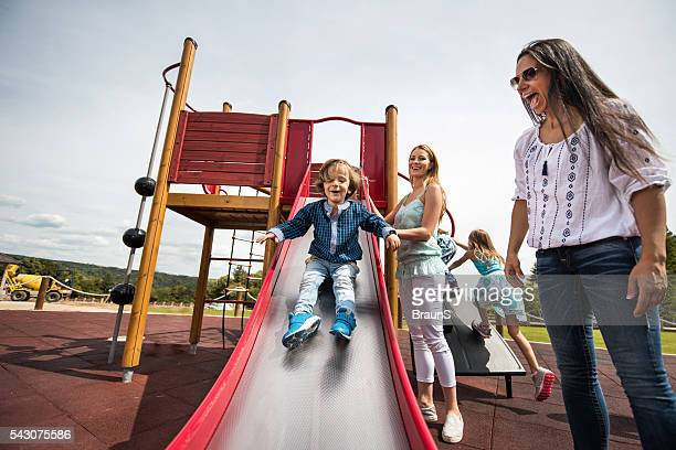 happy women having fun with their children at the playground. - slide play equipment stock pictures, royalty-free photos & images