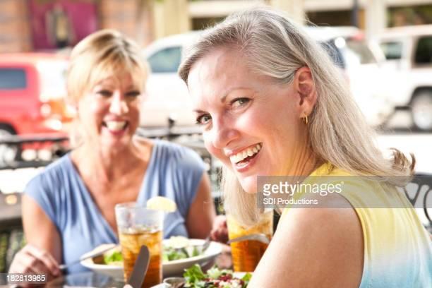 Mujer feliz con el almuerzo en la cafetería al aire libre