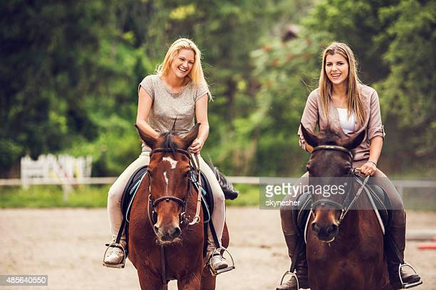 Happy women horseback riding and looking at camera.