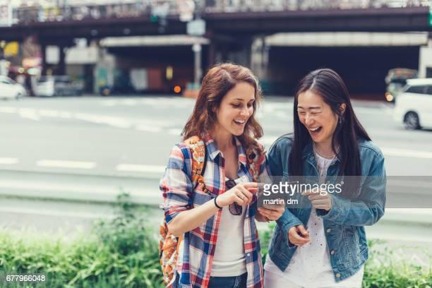 通りでタブレットを使用して東京で幸せな女性 - 観光 ストックフォトと画像