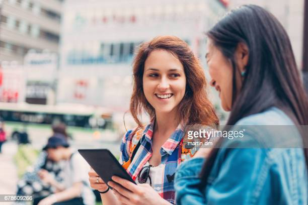 Happy women in Tokyo using tablet at the street
