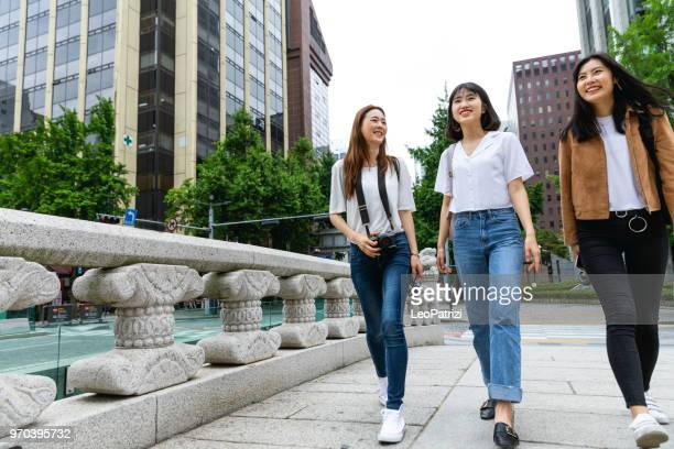 happy women korean friends visiting downtown seoul - cheonggyecheon area - korean teen stock pictures, royalty-free photos & images