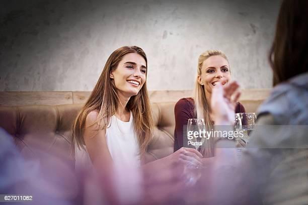 Happy women listening to friend in restaurant