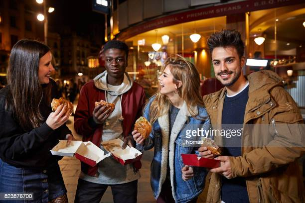 Happy women looking at man eating burger in city