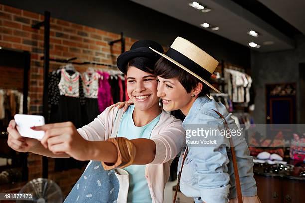 Happy women making selfie in fashion shop