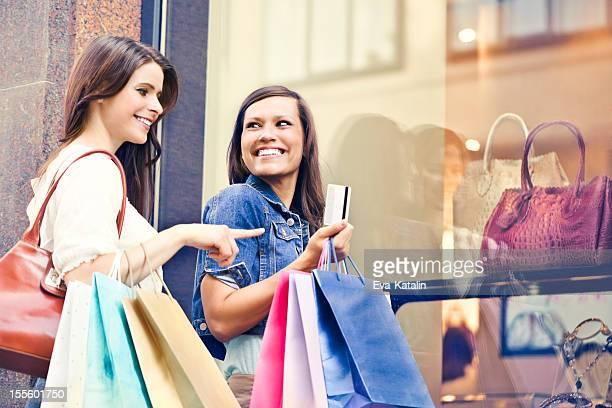 Happy women posing with shopping bags