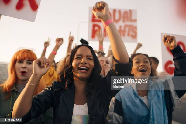 happy women shouting for equal rights while marching together - attivista foto e immagini stock