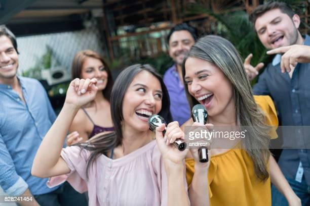 mulheres felizes, cantando em um bar de karaoke - karaokê - fotografias e filmes do acervo