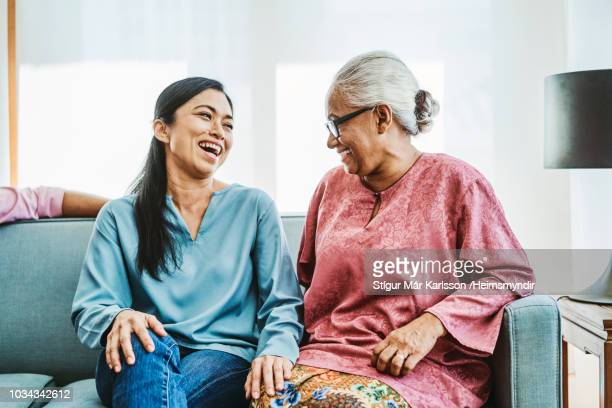 happy women sitting on sofa at home - mother in law stock pictures, royalty-free photos & images