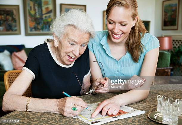 Happy women solving crosswords