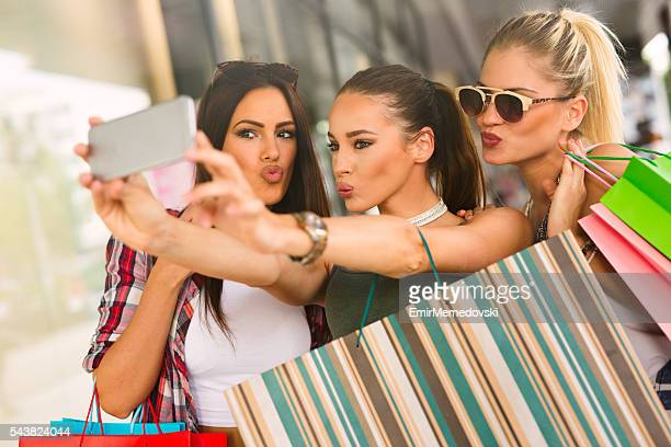 happy women taking a selfie while resting from shopping. - puckering stock pictures, royalty-free photos & images