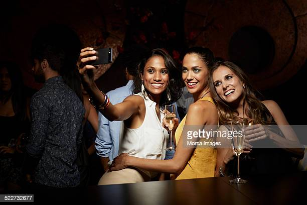 Happy women taking self portrait at nightclub