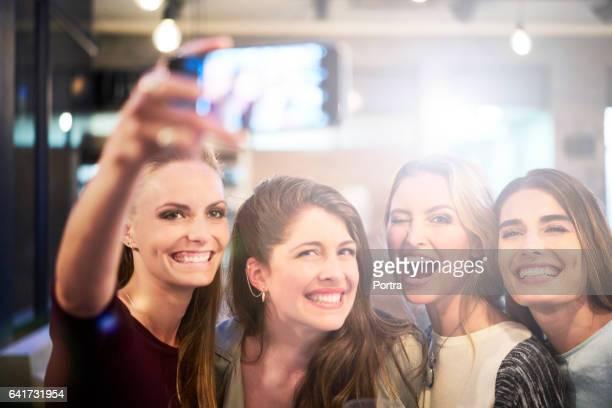 Happy women taking selfie on mobile phone in bar