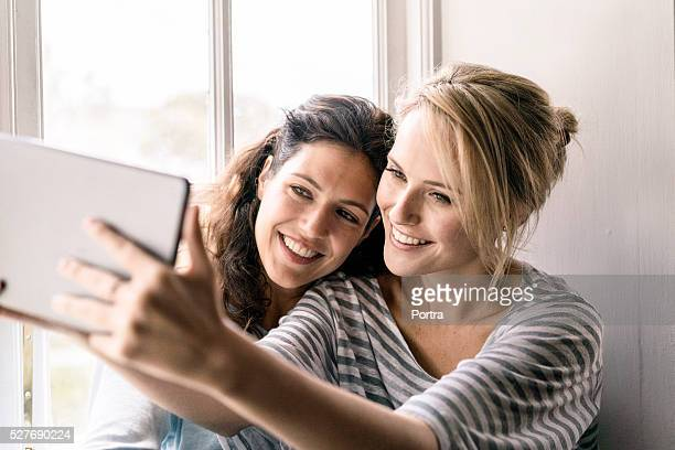 Happy women talking self portrait with digital tablet at home