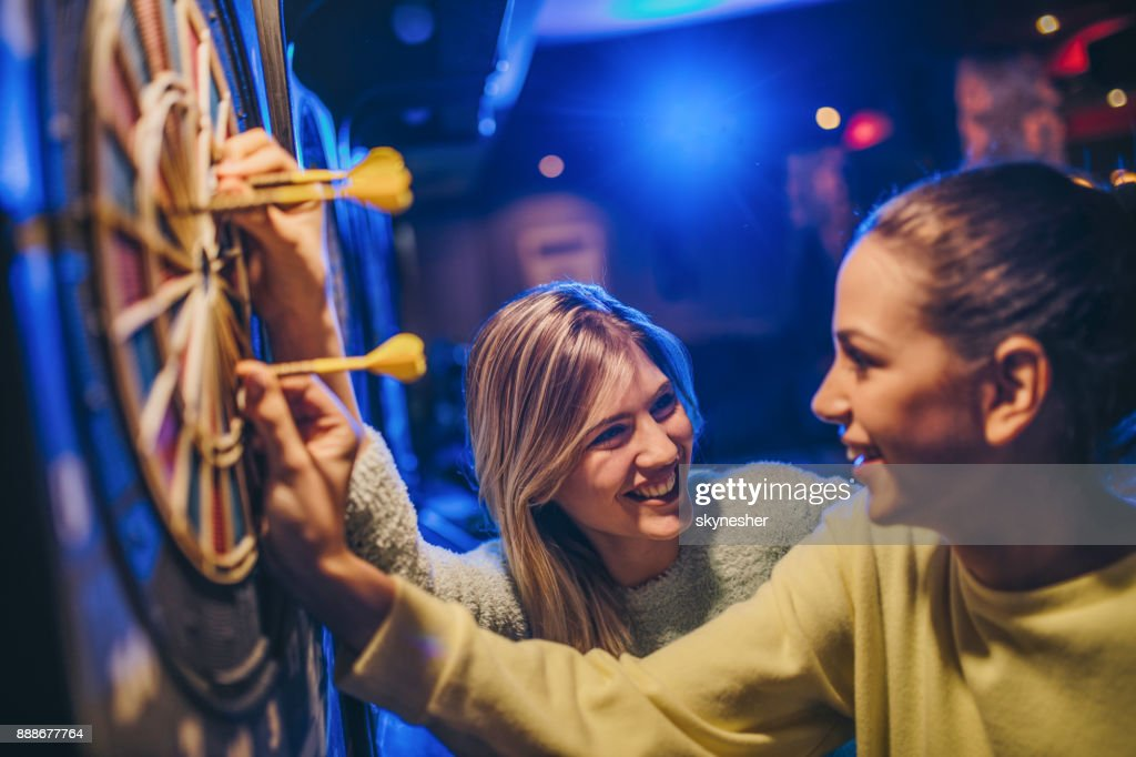 Happy women talking while removing darts from dartboard. : Stock Photo