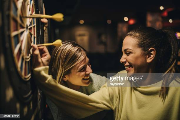 happy women talking while removing darts from dartboard. - darts stock pictures, royalty-free photos & images