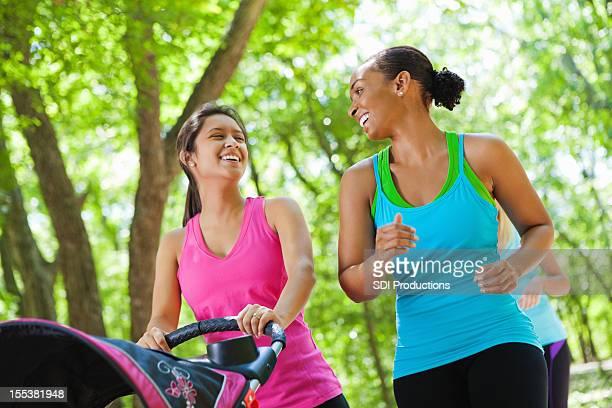 幸せな女性のウォーキング一緒に公園には、ベビー用ベビーカー