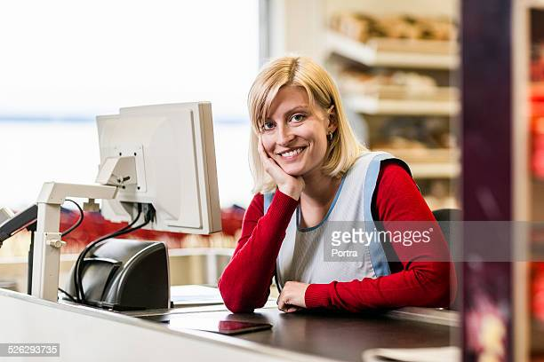 Happy worker at checkout counter in store