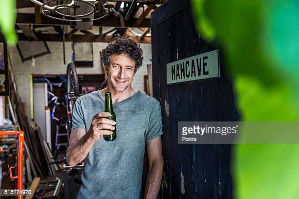 happy worker holding beer bottle in workshop - man cave stock pictures, royalty-free photos & images