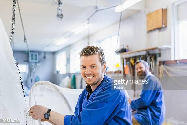 Happy worker preparing net at fishing industry