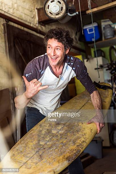 Happy worker showing shaka sign while holding surfboard