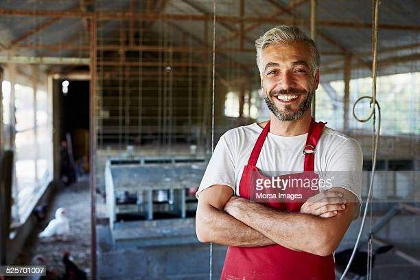 happy worker standing at poultry farm - schürze stock-fotos und bilder