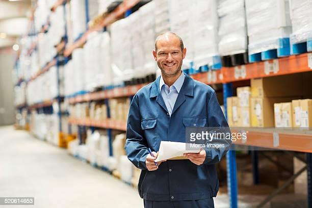Happy worker standing in warehouse