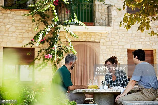 Happy workers having breakfast at yard